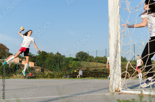 Young female handball player trowing a ball