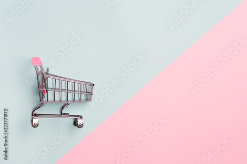 Fotografie, Obraz Close up of supermarket grocery push cart for shopping with black wheels on white background