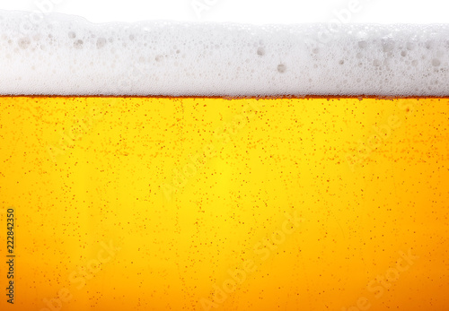 Photographie Close up background of beer with bubbles in glass