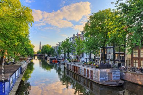 Fototapeta premium Łodzie mieszkalne nad kanałem Prinsengracht światowego dziedzictwa UNESCO z Westerkerk (kościół zachodni) w letni poranek z błękitnym niebem i chmurami oraz lustrzanym odbiciem w Amsterdamie, Holandia