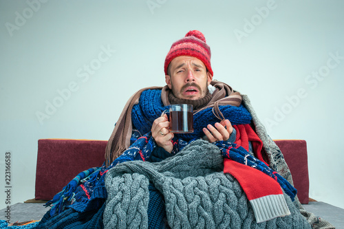 Stampa su Tela Bearded sick man with flue sitting on sofa at home or studio with cup of tea covered with knitted warm clothes