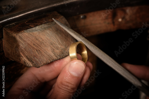 goldsmith hand holds a golden ring on the wooden workbench and works on it with Fototapete