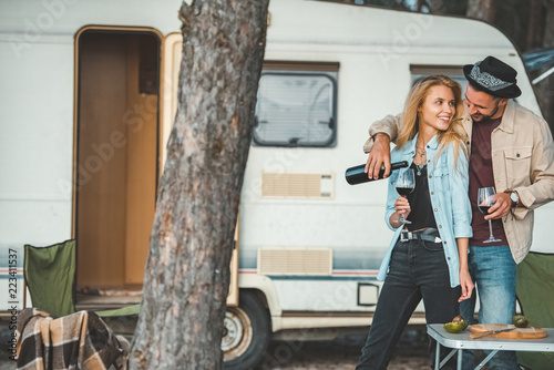 young man pouring red wine for attractive girlfriend near campervan Fototapet