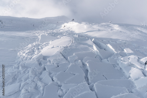 Leinwand Poster Snow avalanche in winter mountains. Danger extreme concept