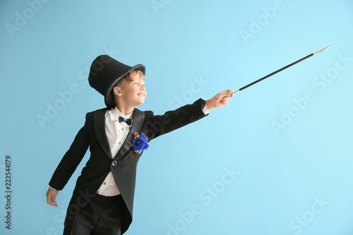 Stampa su Tela Cute little magician showing trick on color background