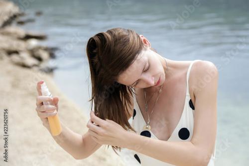 Woman applying sunscreen spray on the beach, hair care protection concept