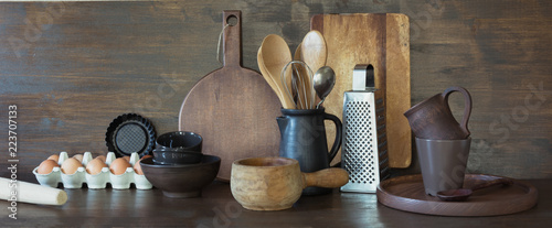 Crockery, clayware, dark utensils and other different stuff on wooden tabletop. Kitchen still life as background for design. Copy space.