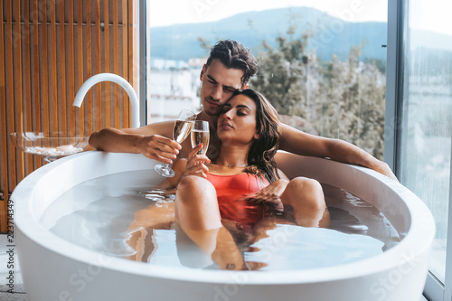 Couple enjoying a bath with champagne Poster Mural XXL