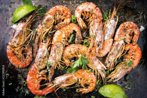 Traditional fried black tiger prawn with lemon as top view on a rustic old board