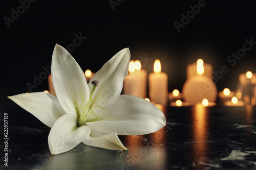 White lily and blurred burning candles on table in darkness, space for text. Funeral symbol