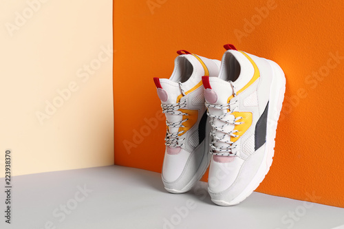 Pair of stylish sneakers near color wall, space for text