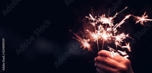 Hand holding burning Sparkler blast on a black bokeh background at night,holiday celebration event party,dark vintage tone