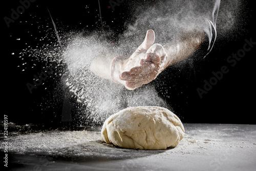 Obraz na plátně Chef scattering flour while kneading dough