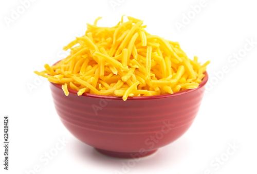 Bowl of Grated Cheddar Cheese on a White Background