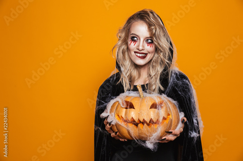Vászonkép European witch woman wearing black costume and halloween makeup holding carved p