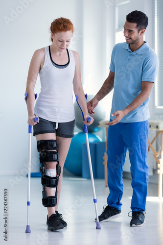 Physiotherapist helping woman with stiffener on the leg walking with crutches Poster Mural XXL