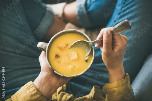Flat-lay of female sitting keeping mug of Fall warming pumpkin cream soup with croutons top view. Autumn vegetarian, vegan, healthy comfort food eating concept