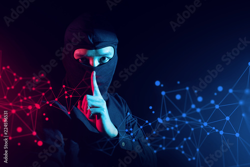 Fotografie, Obraz hacker guy in ninja costume with red and blue light in security hack to digital