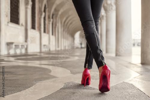 Fototapeta Woman walking in black pants and red high heels