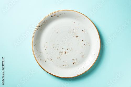 Fototapeta White plate on blue background, from above
