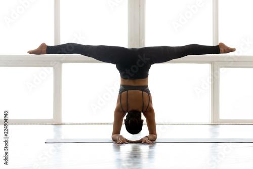 Fotografiet Young yogi attractive woman practicing yoga, doing Pincha Mayurasana exercise, h