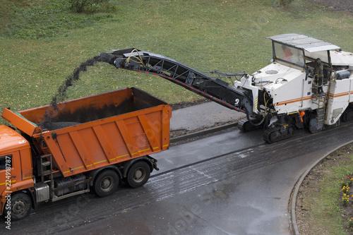 Valokuva Road milling machine removes old asphalt and loads milled asphalt into the dump truck