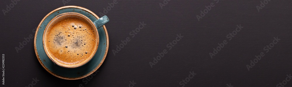 Cup of coffee on black background. Copy space. Top view. Flat lay. Panorama