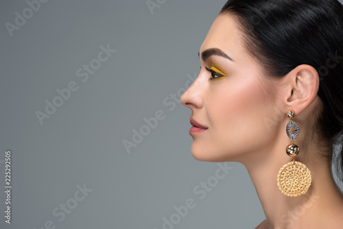 side view of young brunette woman with beautiful earring looking away isolated o Fototapete