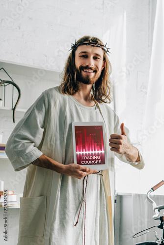 Fotografija happy Jesus in crown of thorns doing thumb gesture and showing digital tablet wi