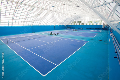 Background shot of modern indoor tennis court interior in blue colors, copy space