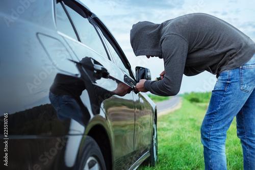 Photo car thief in action, a man in a hood breaks a screwdriver car door