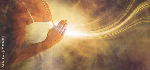 Peaceful prayer sending love and light out -  female in white dress with hands in prayer position and a stream or white light flowing outwards with a rustic golden brown ethereal energy background