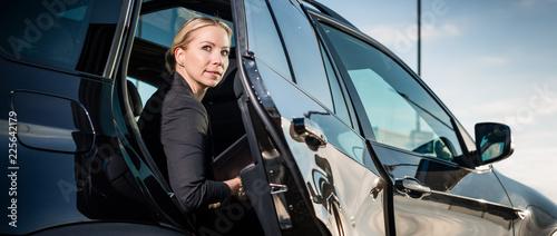 Fotografia, Obraz Portrait of businesswoman sitting inside car with door open