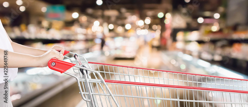 Woman hand hold empty red shopping cart with abstract blur supermarket discount store aisle interior defocused background with bokeh light
