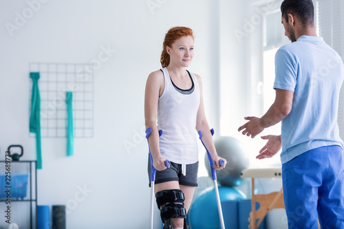 Woman with crutches during rehabilitation with helpful physiotherapist Fototapeta