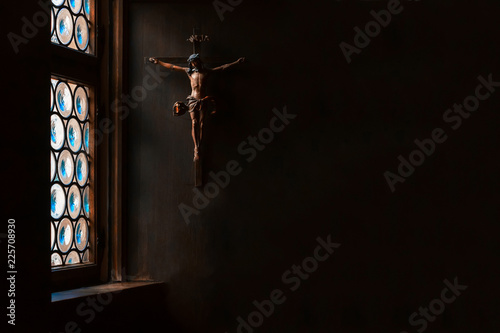 The crucifix, a cross with Jesus hanging on the wall, rays of light gently illuminate it