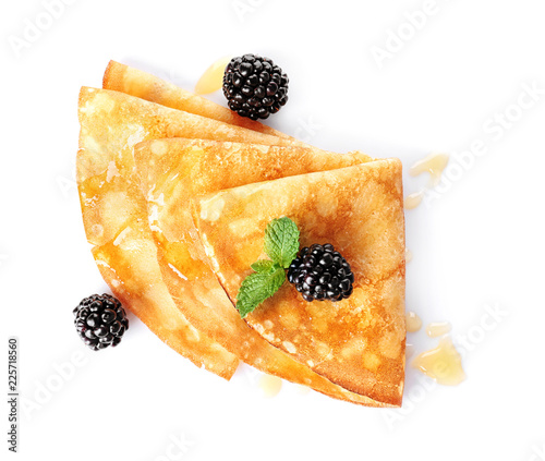 Tasty thin pancakes with maple syrup and berries on white background, top view