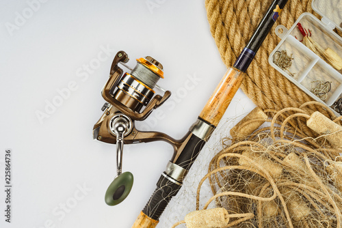 Cuadros en Lienzo top view of fishing rod, nautical rope and plastic box with fishing tackle and b