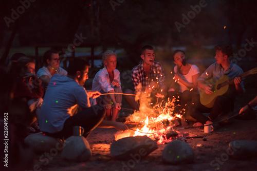 young friends relaxing around campfire Fototapeta
