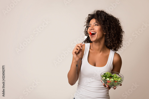 Tableau sur Toile Excited lady eating healthy salad over light background