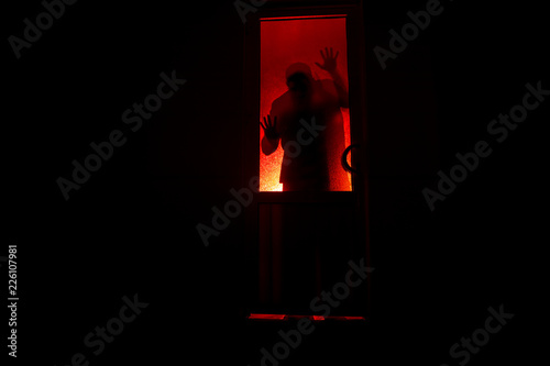 Slika na platnu Silhouette of an unknown shadow figure on a door through a closed glass door