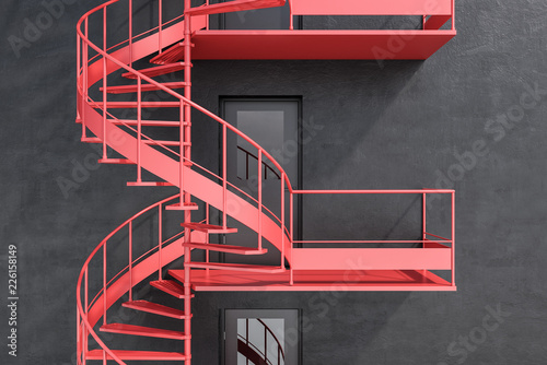 Gray building with red spiral fire escape stairs Fototapeta