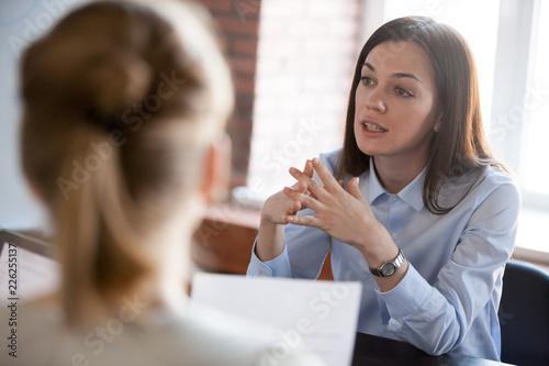 Fotografia Confident focused businesswoman, teacher or mentor coach speaking to business pe