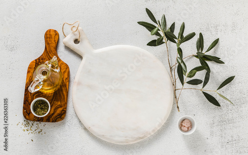 empty white marble cutting board and olive tree branch. table setting.