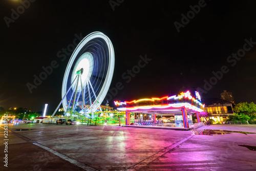 Foto Ferris wheel at amusement park in sunset time / Moving of Ferris wheel at amusem