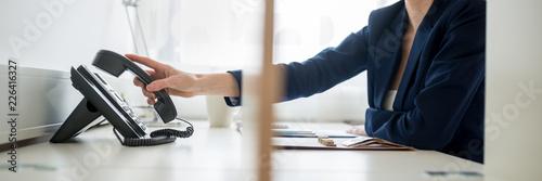 Obraz na płótnie Businesswoman or picking or hanging up  handset