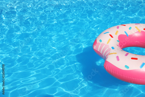 Vászonkép Inflatable ring floating in swimming pool on sunny day