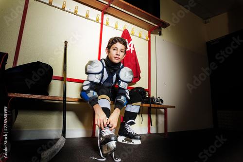 Boy ties hockey skates laces in dressing room