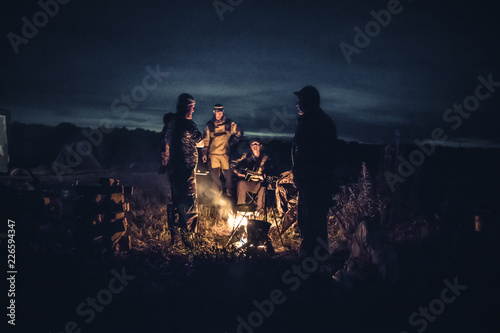 Fotografia, Obraz Group of men people travelers tourist resting camp fire in outdoors camp after l