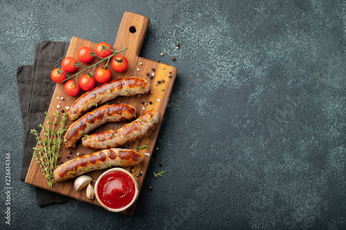 Obraz na płótnie Fried sausages with sauces and herbs on a wooden serving Board